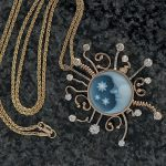 Moon Burst – Carved Moon cameo set in gold surrounded by diamonds.